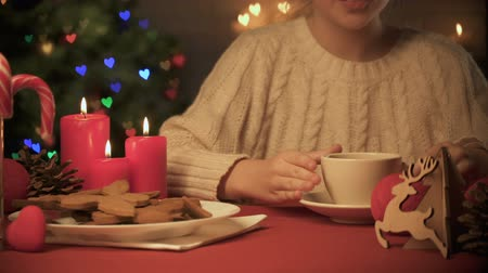 fireplace : Adorable girl smelling and drinking hot cocoa, Christmas decor and cookies Stock Footage