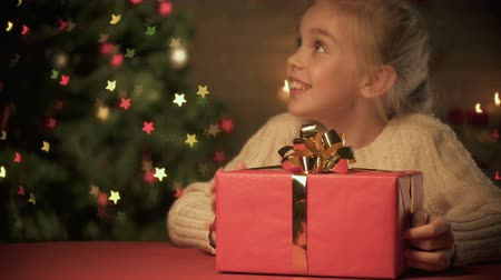 kinderwens : Lady giving excited girl Christmas gift, happy holiday time, tree sparkling