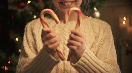 chuches : Smiling girl showing X-mas candies to camera, happy magic holiday time, close-up Archivo de Video