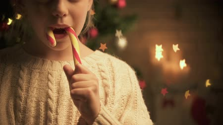 miraculous : Cute child licking traditional X-mas candy smiling to camera decorations glowing