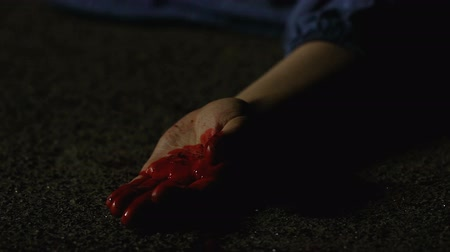 bloody hands : Bloody hand of victim shot dead in street fight, contract killing crime Stock Footage