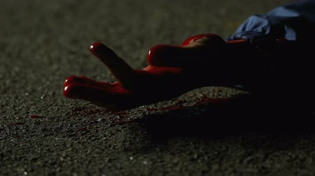 bloody hands : Wounded victim of murderer lying on ground, cruel crime in night street
