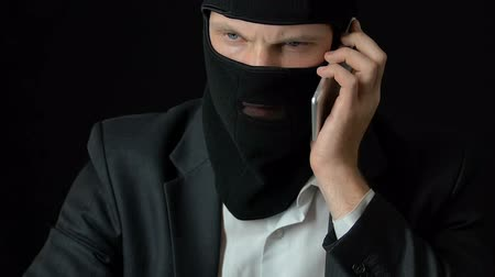 intruder : Rich criminal in balaclava answering phone call, illegal business, blackmail