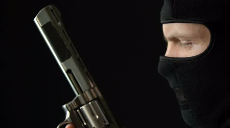 gengszter : Desperate criminal in balaclava holding handgun, preparing for attack, killer