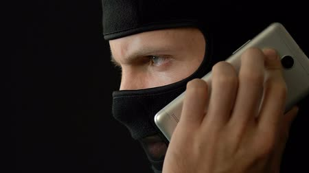 intruder : Terrorist in mask talking on smartphone with crime partner, kidnapping, closeup. Stock Footage