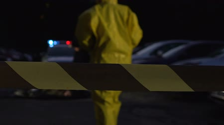 csi : Forensics expert walking to officer near body of poisoning victim at crime scene