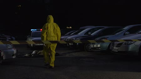 csi : Toxic poisoning crime, forensics expert in protective suit walking to victim Stock Footage