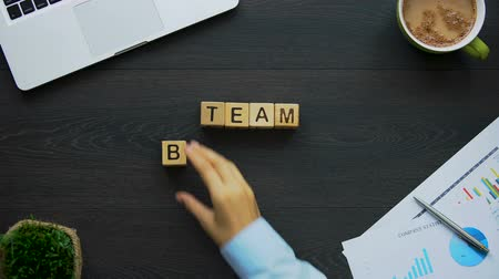 frase : Team building, business woman making phrase of cubes, collective activities
