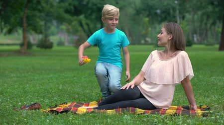 loved : Cute boy presenting wildflowers to mother, pleasant surprise from loved one Stock Footage