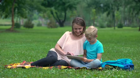 access : Mother and son using tablet computer in park, wireless internet access anyplace Stock Footage