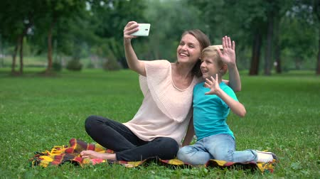 conferencing : Mother and son talking with father via smartphone, video conference outdoors Stock Footage