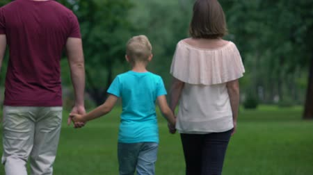 together trust : Family with kid holding hands, walking away, togetherness and family support