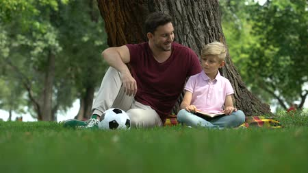 supportive : Father and son reading book in park, man encourages boy to knowledges, family