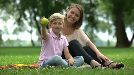 immune : Boy holding apple, sitting with mother in park, concept of healthy nutrition