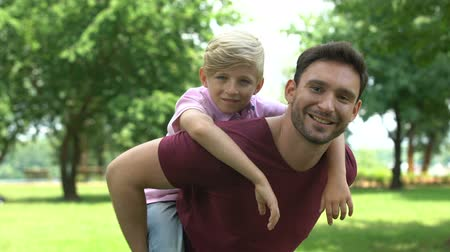 supportive : Father and son enjoying piggyback ride, showing thumbs up, support and trust