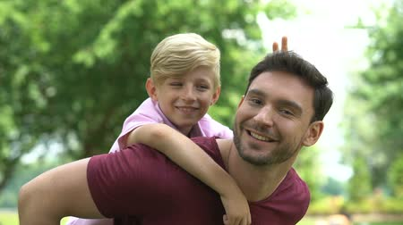otcovství : Dad and son piggyback ride, family resting on weekend in park, happy childhood