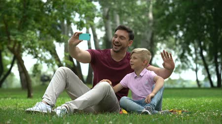 conferencing : Father and son talking with mother via smartphone, video conference outdoors