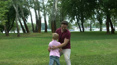 perdão : Dad plays with boy in park, enjoying summer weekend with son, single parent