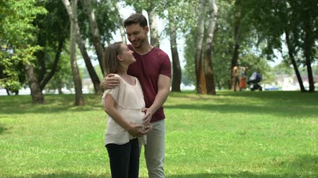 health insurance : Pregnant family posing for camera in park, happy maternity and prenatal care