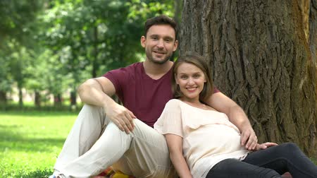 allowance : Pregnant couple sitting in park, smiling into camera, happy maternity, parenting