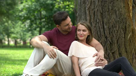 allowance : Happy pregnant couple sitting in park, planning secured family life, welfare Stock Footage
