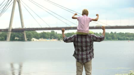 плечи : Dad with son on his shoulders looking at city, showing strength and confidence