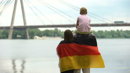 brasão : Family wrapped in German flag looking at bridge, immigration, independence day