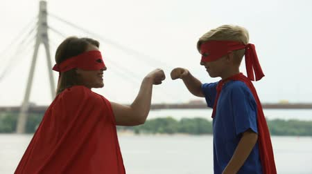 supportive : Mom and son in superhero costumes punching fists, concept of teamwork, success Stock Footage