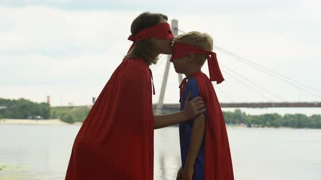 supportive : Mom in superhero costume kisses son forehead, embracing, support in beginnings Stock Footage