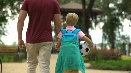 after school : Father walking home with son after school, discussing sport classes, football