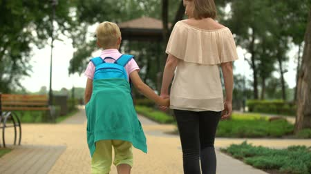 after school : Mother and child walking home after classes, son talking about day at school Stock Footage