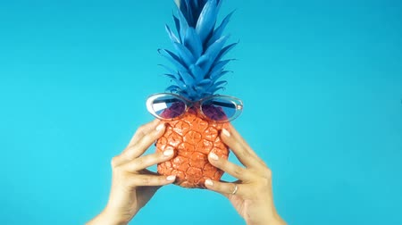 ananas : Female hands holding funny colored pineapple with sunglasses, time for vacation