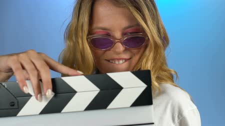 cinematography : Young woman having fun playing with clapperboard, drive and licentiousness