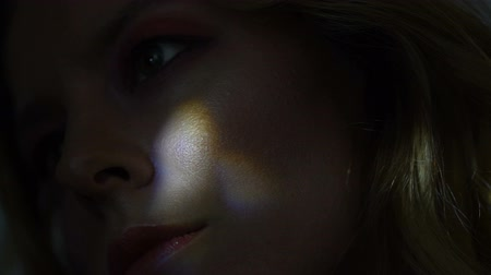 perfil : Beautiful female face illuminated by colorful light beams darkness, closeup Stock Footage