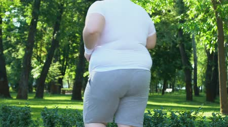 willpower : Obese man jogging to lose extra weight, active lifestyle and motivation. Stock Footage