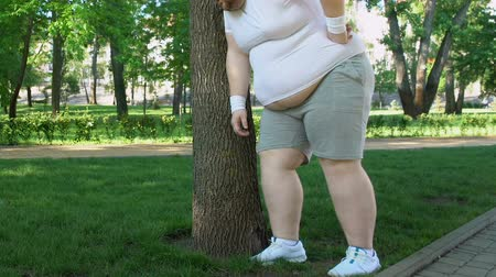 willpower : Fat man breathing heavily standing near tree, doing sports to lose weight faster Stock Footage