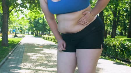empresárias : Obese girl feeling sharp pain in left back during jogging, exhausting workout