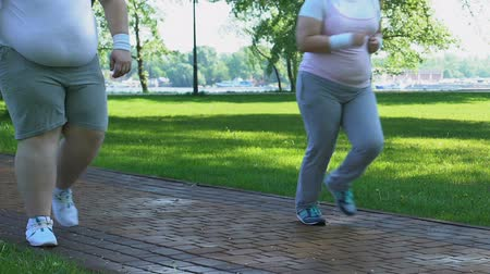 willpower : Woman running while man slowly walking in park, daily trainings for obese people.