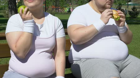 willpower : Happy fat girl eating apple after workout, laughing at obese man with burger Stock Footage