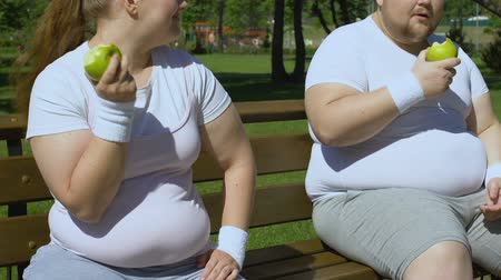 dietético : Overweight couple eating juicy apples after workout, healthy snack. Stock Footage