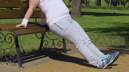 paunchy : Chubby woman doing crunches leaning on bench in park, tiresome training program Stock Footage
