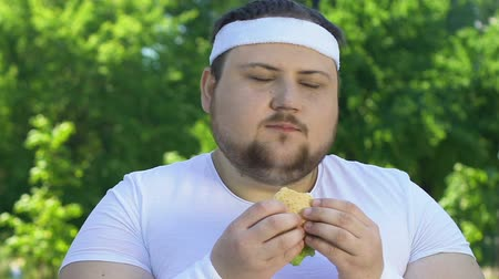 круглолицый : Fat man eating burger after workout, addicted to junk food.