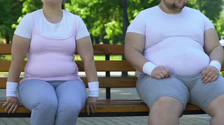 esteem : Funny fat woman and man sitting on bench, flirting to each other, feelings