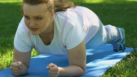 daily : Plump girl doing plank outdoor, endurance and strength, healthy lifestyle