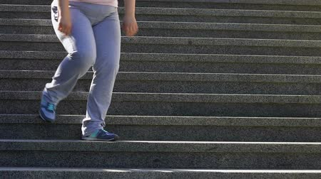 tükenme : Exhausted plump girl slowly walking down stairs after workout.