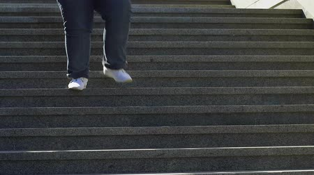 vyčerpání : Pot-bellied guy slowly walking down stairs, listening to music, obesity problems