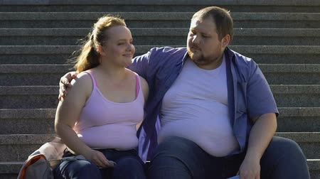 fondness : Overweight male hugging his beautiful girlfriend, resting on stairs outdoor date