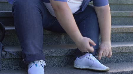 chunky : Obese man tying shoelaces with difficulty, problems with extra weight, health Stock Footage