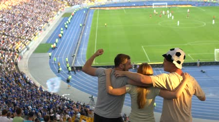 tribune : Male friends cheering for football team, happy for winning goal, kissing girl