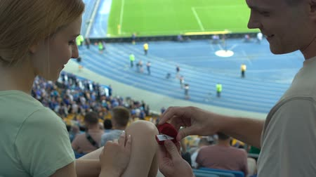 stadion : Romantic marriage proposal during football match, pleasant surprise, slow-mo